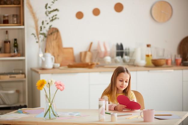 Portrait grand angle de jolie fille tenant une carte en forme de coeur et souriant alors qu'il était assis à table dans un intérieur confortable, espace copie