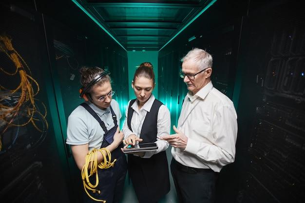 Portrait en grand angle de personnes utilisant une tablette dans la salle des serveurs tout en effectuant des travaux de maintenance dans un centre de données, espace de copie