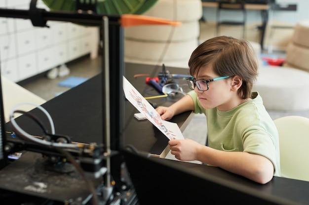 Portrait en grand angle d'un petit garçon utilisant une imprimante 3d pendant le cours d'ingénierie et de robotique à l'école moderne, espace de copie