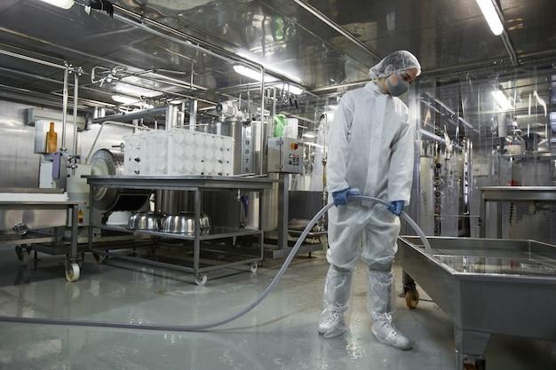 Portrait grand angle sur toute la longueur d'une travailleuse lavant l'équipement dans une usine de production d'aliments propres, espace pour copie