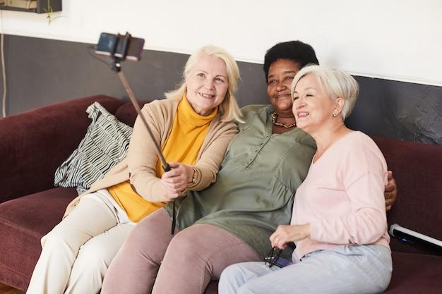 Portrait en grand angle de trois femmes âgées prenant un selfie dans une maison de retraite à l'aide d'un bâton de selfie