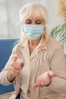 Portrait grand-mère avec masque à l'aide de désinfectant pour les mains