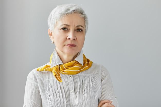 Portrait de grand-mère sérieuse avec des rides et des cheveux gris courts posant en posture fermée, les bras croisés, ayant un regard strict, fronçant les sourcils, mécontent de la mauvaise conduite de ses petits-enfants