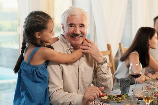 Portrait de grand-père heureux souriant tandis que sa petite-fille l'embrassant pendant le dîner à la maison