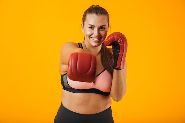 Portrait de grande sportive joyeuse en soutien-gorge sportif portant des gants de boxe pratiquant, isolé sur fond jaune