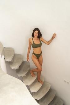 Portrait grandeur nature d'une fille bronzée mince et sérieuse, debout dans les escaliers d'un lodge