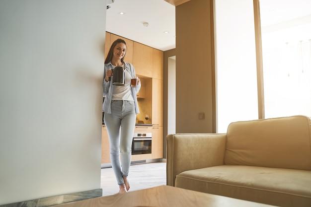 Portrait grandeur nature d'une fille joyeuse tenant une tasse de tisane à la main