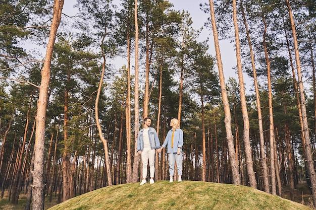 Portrait grandeur nature d'un jeune couple caucasien debout sur une colline dans une forêt de conifères