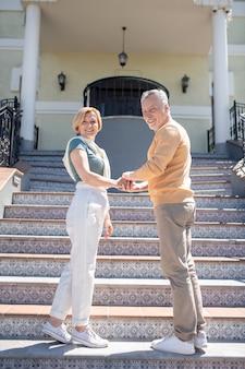 Portrait grandeur nature d'une jolie femme joyeuse et de son beau conjoint masculin debout sur les marches à motifs