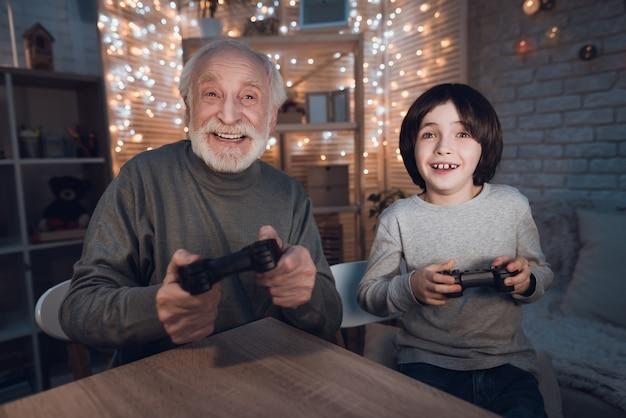 Portrait grandson jouer au jeu vidéo avec grand-père