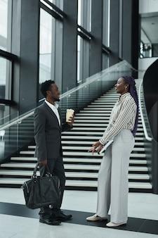 Portrait graphique complet de deux hommes d'affaires afro-américains discutant joyeusement tout en se tenant dans le hall de bureau