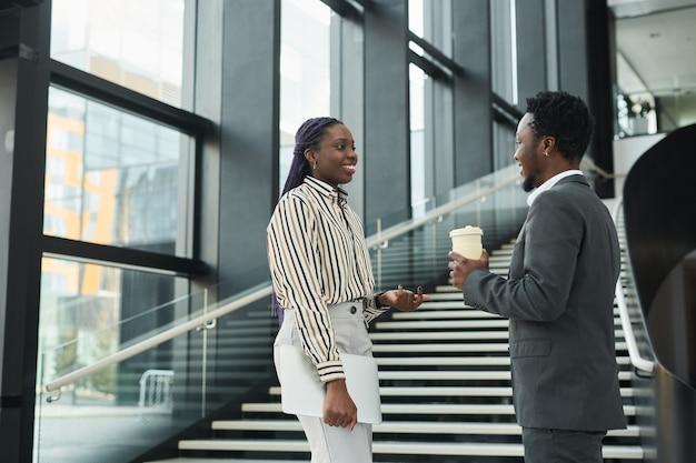 Portrait graphique à la taille de deux hommes d'affaires afro-américains discutant joyeusement en se tenant debout dans le hall de bureau, espace pour copie