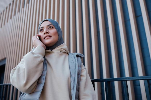 Portrait graphique à la taille d'une femme moderne du moyen-orient parlant par smartphone en ville, espace pour copie