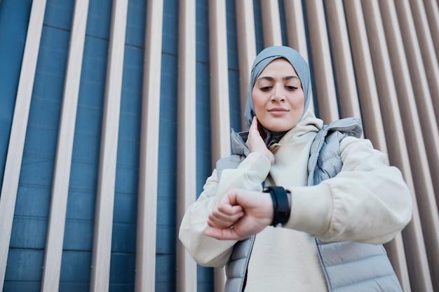 Portrait graphique à la taille d'une femme moderne du moyen-orient vérifiant la montre intelligente pendant la course du matin, espace de copie