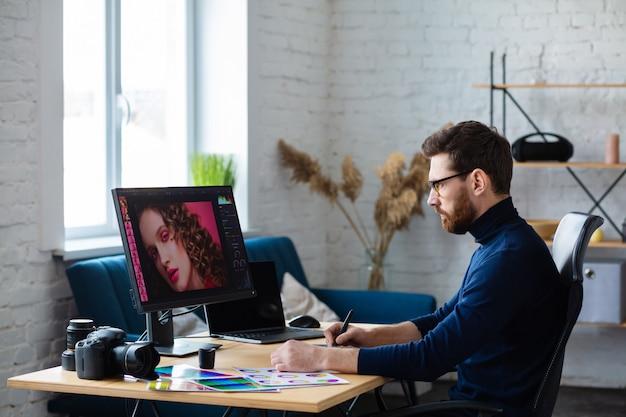 Portrait de graphiste travaillant au bureau avec ordinateur portable, moniteur, tablette graphique et palette de couleurs.