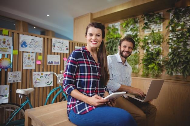 Portrait de graphistes assis sur un bureau à l'aide d'un ordinateur portable et d'une tablette numérique