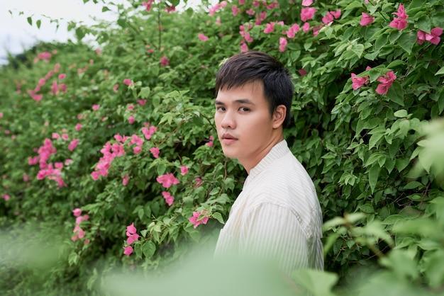 Portrait de grave beau jeune homme debout sur fond d'arbre vert, l'été dans la ville