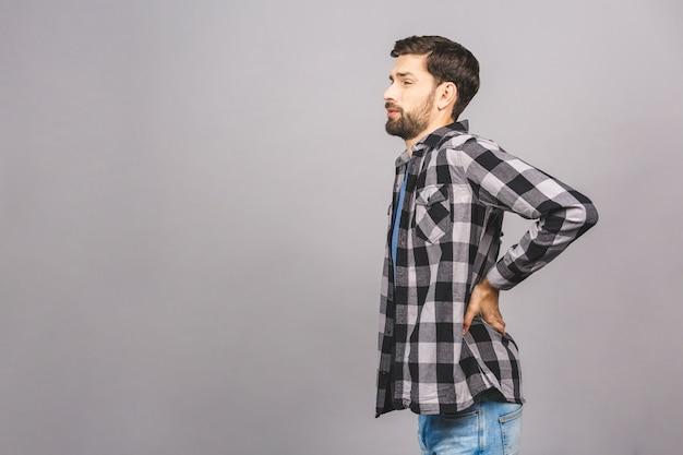 Portrait de grimace triste bouleversé mécontent de graves douleurs dans le dos homme portant casual isolé sur gris gris mur copie-espace.