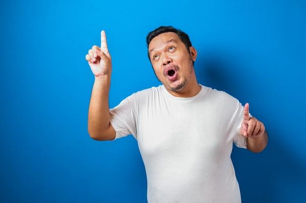 Portrait d'un gros homme asiatique drôle en t-shirt blanc souriant et dansant joyeusement