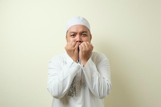 Portrait de gros homme musulman asiatique se ronger les ongles comme s'il avait peur de quelque chose de mal
