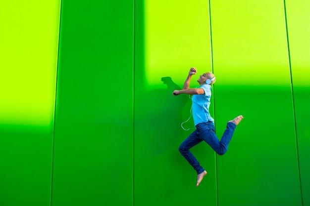 Portrait et gros plan d'un adolescent, d'un millénaire ou d'un jeune homme sautant de la musique avec des écouteurs