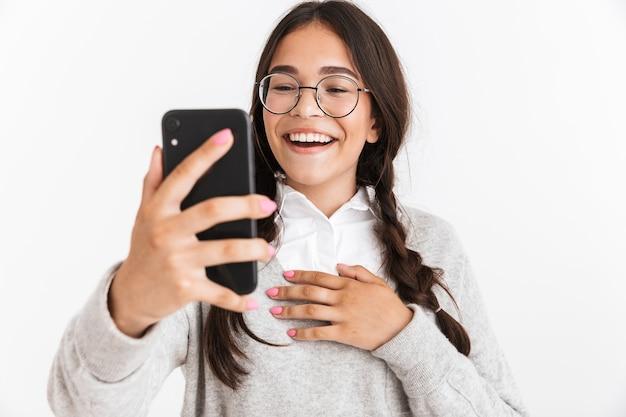 Portrait en gros plan d'une adolescente heureuse portant des lunettes et un uniforme scolaire se réjouissant tout en parlant sur un smartphone isolé sur un mur blanc