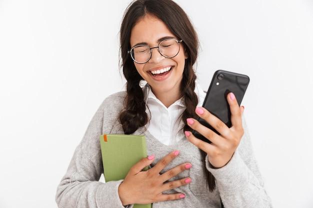 Portrait en gros plan d'une adolescente joyeuse portant des lunettes en riant tout en étudiant des livres et un smartphone isolé sur un mur blanc