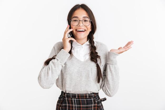 Portrait en gros plan d'une adolescente surprise portant des lunettes et un uniforme scolaire se réjouissant tout en parlant sur un smartphone isolé sur un mur blanc