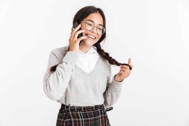 Portrait en gros plan d'une adorable adolescente portant des lunettes et un uniforme scolaire se réjouissant tout en parlant sur un smartphone isolé sur un mur blanc