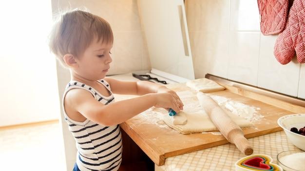 Portrait en gros plan d'un adorable petit garçon de 3 ans roulant la pâte de blé avec un rouleau à pâtisserie et coupant des biscuits avec un coupeur en plastique spécial. chuld cuisson et cuisson sur cuisine