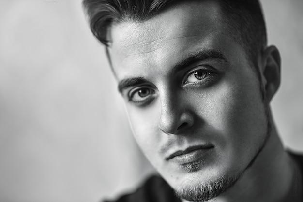 Portrait de gros plan de beau jeune homme au visage sérieux