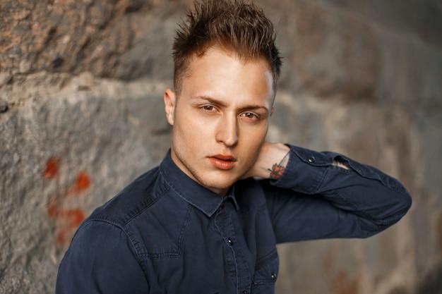 Portrait en gros plan d'un beau jeune homme dans une chemise bleue près d'un mur de pierre