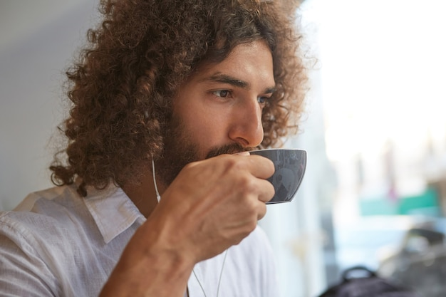 Portrait de gros plan de beau jeune homme non rasé bouclé, boire du café dans un café et écouter de la musique avec des écouteurs, à la recherche réfléchie et calme