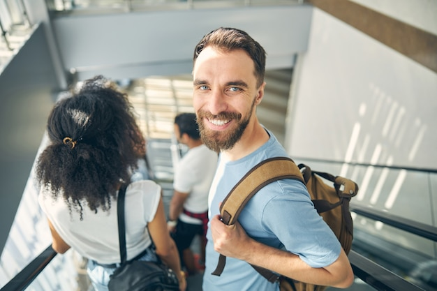 Portrait en gros plan d'un beau mâle en chemise bleue avec sac à dos sur l'épaule allant au départ de la porte pour voyager en avion