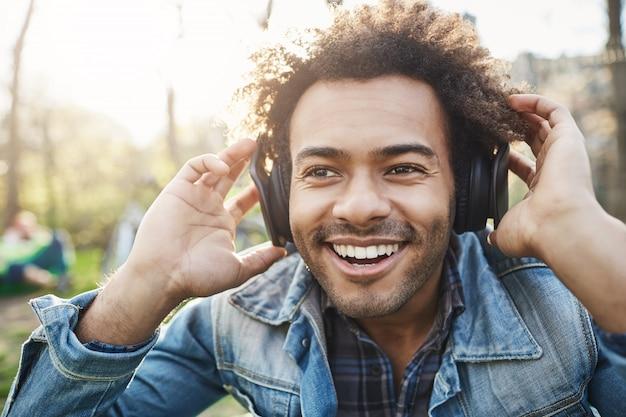 Portrait de gros plan de beau mec à la peau sombre non rasé tenant la main sur un casque tout en écoutant de la musique et en étant excité, regardant de côté, assis dans le parc.
