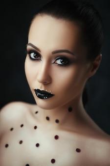 Portrait en gros plan d'un beau modèle avec du maquillage sombre