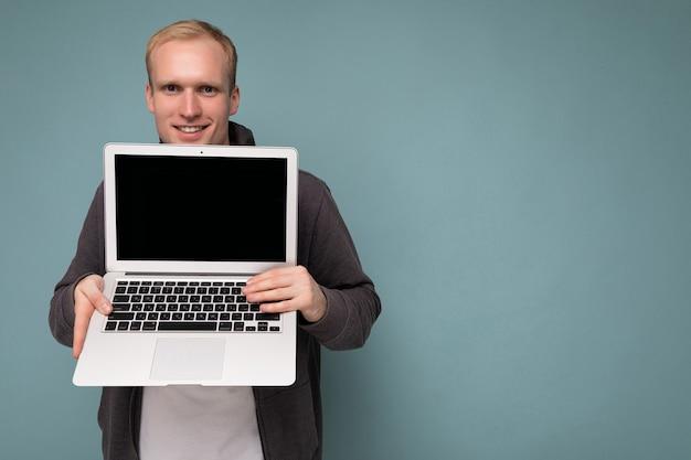 Portrait en gros plan d'un bel homme blond souriant tenant un ordinateur portable avec un écran de moniteur vide