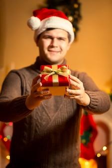 Portrait en gros plan d'un bel homme souriant en bonnet de noel tenant une boîte-cadeau rouge