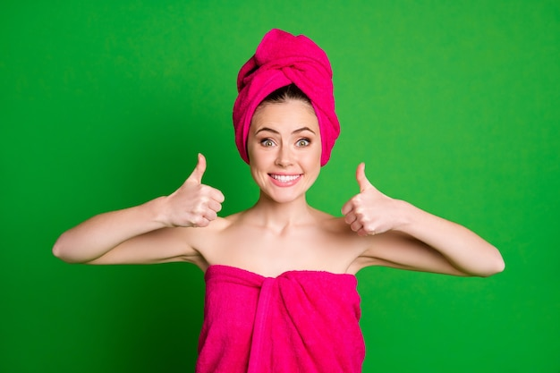 Portrait en gros plan d'une belle dame joyeuse et heureuse portant un turban montrant une annonce de pouce isolée sur un fond de couleur vert vif