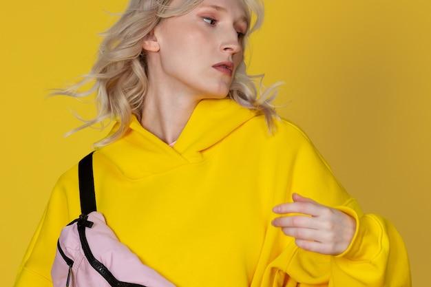 Portrait en gros plan d'une belle étudiante blonde caucasienne dans un sweat à capuche jaune