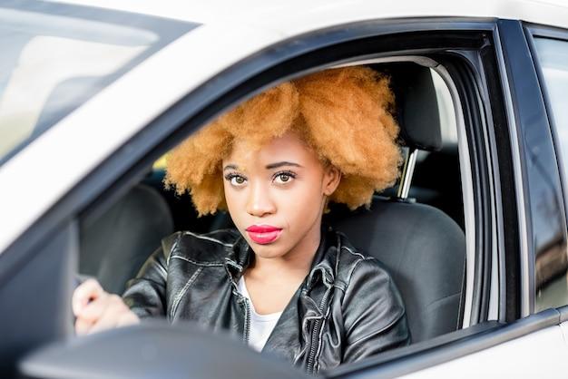 Portrait en gros plan d'une belle femme africaine aux cheveux bouclés en blouson de cuir au volant d'une voiture