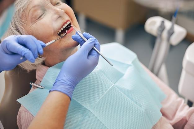 Portrait en gros plan d'une belle femme âgée ayant un contrôle dentaire dans un cabinet dentaire