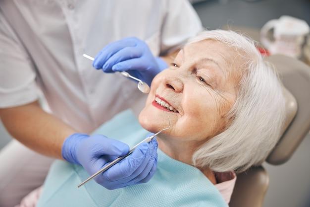 Portrait en gros plan d'une belle femme âgée vérifier et consulter un dentiste au cabinet dentaire