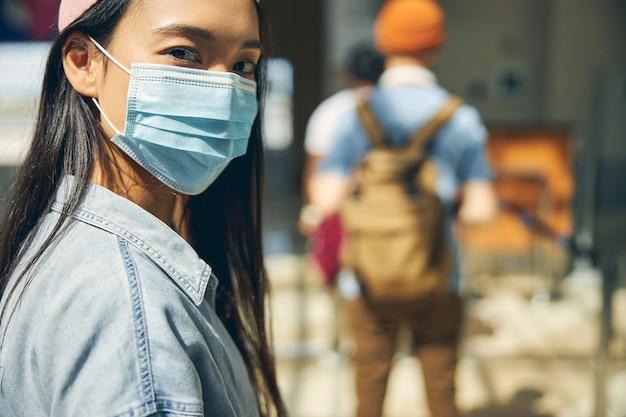 Portrait en gros plan d'une belle femme asiatique regardant l'appareil photo à l'aéroport international