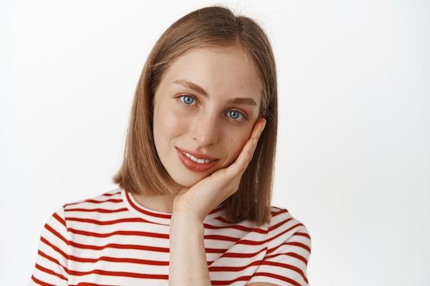 Portrait en gros plan d'une belle femme blonde aux yeux bleus et à la peau du visage propre et éclatante, toucher son visage et sourire mignon à l'avant, concept de soins de la peau et de cosmétiques, mur blanc