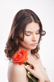 Portrait en gros plan d'une belle femme brune avec une rose rouge à la main