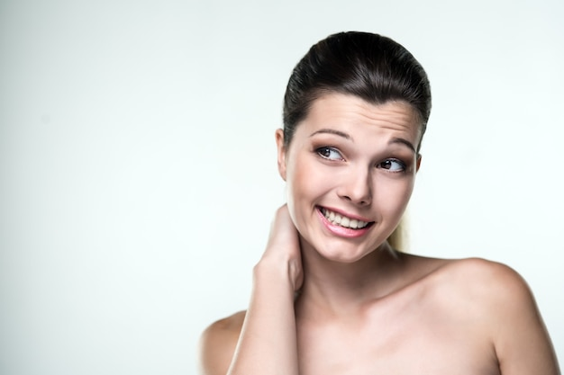 Portrait en gros plan d'une belle femme avec une expression d'émotions regarde de côté vers la gauche sur un fond clair