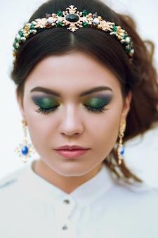 Portrait de gros plan de la belle femme avec un maquillage lumineux et portant des bijoux.