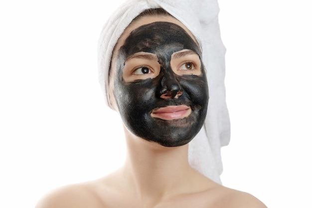 Portrait en gros plan belle femme avec masque facial noir sur fond blanc, fille avec une serviette blanche sur la tête, sourire satisfait et heureux
