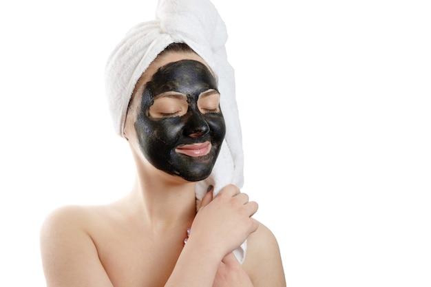 Portrait en gros plan belle femme avec masque facial noir sur fond blanc, fille avec une serviette blanche sur la tête, yeux fermés satisfaits et heureux